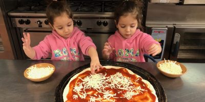 Two pre-schoolers making pizza