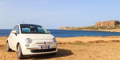 Little white Fiat car parked on Italian beach
