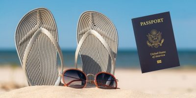 Passport with Sandals and sunglasses on beach